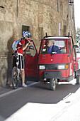 Mountainbikerin vor einem Transporter in Panicale, Umbrien, Italien, Europa
