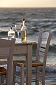 Table with wine bottle and glass on the waterfront at dusk, Little Venice, Mykonos Town, Greece, Europe