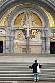 Woman praying in front of the Rosary Basilica, Lourdes. Hautes-Pyrenees, Midi-Pyrenees, France