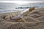A bottle containing a message lies on a beach at sunset