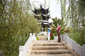 Young Chinese woman and German tourist talking on a bridge at Lianhuachi park, Kunming, Yunnan, People's Republic of China, Asia