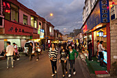 Young people and students at YuanXi street at dusk, shopping street with cafes and restaurants, Kunming, Yunnan, People's Republic of China, Asia