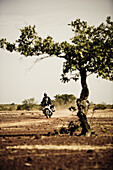 Man on motorcycle riding on a dirt road driving through barren landscape, Mali, Africa