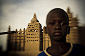 African boy in front of the mosque of Djenna, Mali, Africa