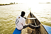African man with german football shirt on a boat on the river Niger, Mopti, Mali, Africa