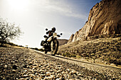 Man on motorcycle on rough-textured tarred road, Mali, Africa