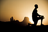 Kneeling boy in front of rock formation at sunset, Hombori, Mali, Africa