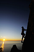 silhouette of a woman climbing a steep rock face at the Mediterranean, sunset in the background, natural park Porto Venere, national park Cinque Terre, UNESCO world heritage site, Liguria, Italy