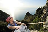 Woman climbing a rock face high above the Mediterranean sea, natural park Porto Venere, national park Cinque Terre, UNESCO world heritage site, Liguria, Italy