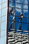 Window cleaner cleaning the outside of a skyscaper building, Chicago, Illinois, USA
