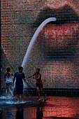 Teenagers playing in The Crowne Fountain by Jaume Plensa, Millenium Park, Chicago, Illinois, USA