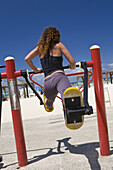 Woman exercising on public exercisers on the beach, Tel Aviv, Israel, Middle East