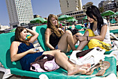 Young Isreali women relaxing on sunloungers, Gordon Beach, Tel Aviv, Israel, Middle East