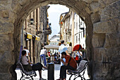Two persons sitting in an archway, old town, Aosta, Aosta Valley, Italy