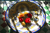 Roses in a porcelain bowl in the sunlight, Riad Kaiss, Marrakech, Morocco, Africa