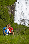 Couple embracing each other on pasture, waterfall in background, Zillertal, Tyrol, Austria