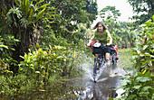 Frau fährt durch flaches Gewässer, Nationalpark Masoala, Madagaskar