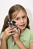 Girl holding a young domestic cat, Bavaria, Germany