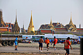 Boys playing football on the esplanade Sanam Luang in front of Wat Phra Kaeo, Bangkok, Thailand, Thailand, Asia