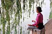 Woman doing yoga exercises near Hoan Kiem lake, old town of Hanoi, Vietnam