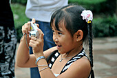 Young girl taking a photograph in the Literature Tempel, Ba Dinh-Quarter, Hanoi, Vietnam