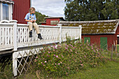 A girl sitting on the railing of a farmhouse, Vaesternorrland, Sweden, Europe