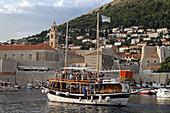 Tourist excursion ship entering old port of Dubrovnik harbour, Croatia, Europe