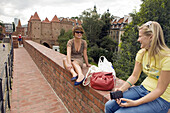 Young women sitting on the Old Town Wall, Warsaw, Poland, Europe