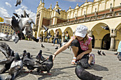 Girl feeding pigeons main market square Rynek Glowny in front of cloth hall, Krakow, Poland, Europe