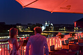 Young couple on the roof terrace of Hotel Poleski at night, Krakow, Poland, Europe