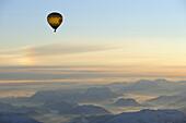 Aerial view of hot-air balloon above Kaisergebirge range at sunrise, Berchtesgaden range in background, Tyrol, Austria, Europe