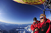 Two persons in hot-air balloon looking towards snow-covered alps, aerial photo, South Tyrol, Italy, Europe