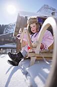 Female toddler on sledge near hut, Galtuer, Paznaun valley, Tyrol, Austria