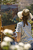 One woman with straw hat and colorful blouse creating landscape oil painting in summer