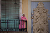 Old woman with pink bathrobe looking away from the balcony