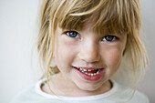 Close up of a blond little girl with fringe naive eyes and open mouth