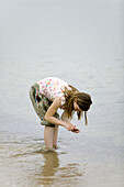 Girl is looking for stones in the water´s edge