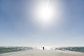 Man stands on a beach, the farthest headland where Skagerrak and the Kattegatt meet, Skagen, Jutland, Denmark