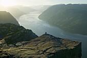 Man stands on Prekkestolen, Lysefjorden, Lyse fjord, Norway