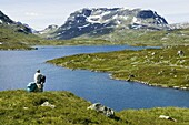 Man with backpacker is sitting on a stone a looking out on water and mountains, Hardangervidda, Norway