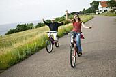 Two girls riding bikes, (MR)