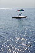 Chair and umbrella on raft in the sea