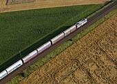 Train drives through agriculture landscape