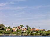 Red houses with Swedish flags in archipelago, Karlskrona, Blekinge, Sweden