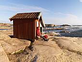 Woman sits by red hut on cliffs, Bohuslan, Sweden