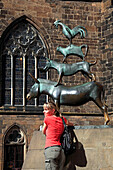 Young woman posing in front of the Bremen town musicans, Hanseatic City of Bremen, Germany, Europe