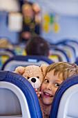 Boy with teddy bear in an airplane, Munich airport, Bavaria, Germany