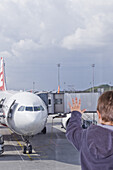 Boy watching airplane on airfield, Munich airport, Bavaria, Germany