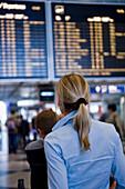Woman reading flight-information board, Munich airport, Bavaria, Germany
