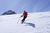 Woman downhill skiing, Granatspitze in background, Granatspitz mountain range, Hohe Tauern, Salzburg, Austria